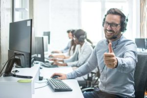 Cheerful employee using VoIP service